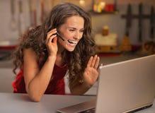 愉快的妇女有在膝上型计算机的录影闲谈在厨房 库存图片