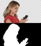 愉快的妇女浏览媒介或发短信在一流动智能手机,阿尔法通道 库存照片