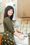愉快的妇女清洗煤气炉与海绵 免版税库存图片
