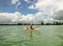 愉快的妇女游泳在海 免版税库存图片