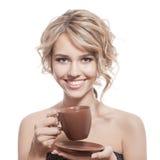 年轻愉快的妇女用一份芳香咖啡在手上。隔绝 免版税库存图片