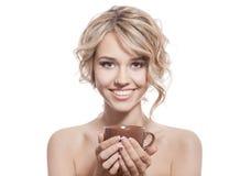 年轻愉快的妇女用一份芳香咖啡在手上。隔绝 免版税图库摄影
