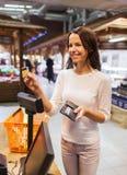 愉快的妇女用信用卡买的食物在市场上 库存照片
