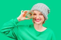 愉快的妇女用反对她的眼睛的五颜六色的多福饼在淡色绿色背景 免版税库存图片