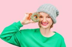 愉快的妇女用反对她的眼睛的五颜六色的多福饼在粉红彩笔背景 免版税库存照片
