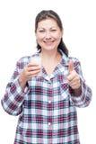 愉快的妇女用在一块玻璃的牛奶在白色的床前 库存照片