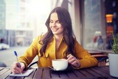 愉快的妇女用在咖啡馆的笔记本饮用的可可粉 图库摄影