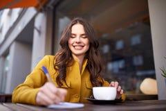 愉快的妇女用在咖啡馆的笔记本饮用的可可粉 免版税图库摄影