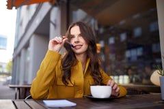 愉快的妇女用在咖啡馆的笔记本饮用的可可粉 免版税库存照片