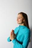 年轻愉快的妇女用在胸口附近的祈祷的手 图库摄影