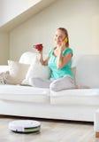 愉快的妇女用智能手机饮用的茶在家 免版税库存照片