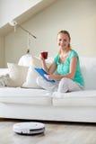 愉快的妇女用片剂个人计算机饮用的茶在家 免版税库存照片