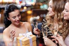 愉快的妇女用香槟和礼物在夜总会 免版税库存照片
