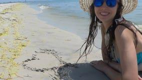 愉快的妇女画在海海滩的湿沙子的爱标志 股票录像