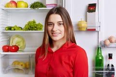 愉快的妇女画象充分站立近的冰箱产品,搜寻食物,去做早餐逗人喜爱的女性近的被打开的r 免版税库存图片