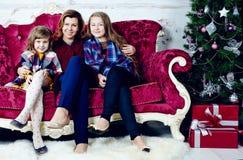 愉快的妇女画象有两个女儿的坐沙发 库存图片