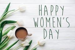 愉快的妇女的天在郁金香和咖啡的文本标志在白色木 免版税库存照片