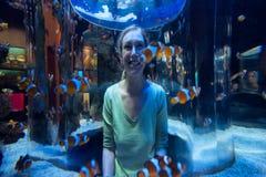 愉快的妇女看小丑鱼通过玻璃 免版税库存图片