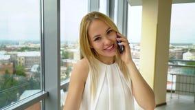 愉快的妇女看照相机和谈话在电话有都市风景的在窗口后 股票录像