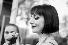 愉快的妇女看看杯形蛋糕在巴黎,法国,食物 有松饼蛋糕的,快餐肉欲的妇女 食物,点心,快餐 beauvoir 免版税库存图片