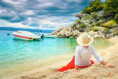 愉快的妇女穿着红色裙子和坐海滩 库存照片