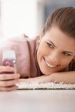 愉快的妇女纵向有移动电话的 库存照片