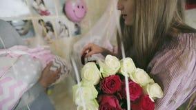 愉快的妇女考虑礼物 抱着他的胳膊的丈夫新出生的婴孩 影视素材