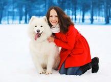 愉快的妇女获得与白色萨莫耶特人狗的乐趣户外在冬日 免版税库存图片