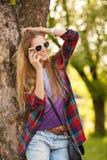 年轻愉快的妇女谈话在手机在夏天城市公园 太阳镜的美丽的现代女孩有智能手机的,室外 库存图片