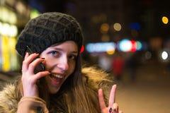 年轻愉快的妇女谈话在手机在晚上在冬天 免版税库存照片