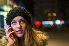 年轻愉快的妇女谈话在手机在晚上在冬天 库存照片