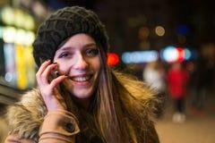 年轻愉快的妇女谈话在手机在晚上在冬天 库存图片