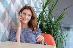 年轻愉快的妇女谈话在有朋友的手机,当单独坐在现代咖啡店内部,微笑时 免版税库存图片