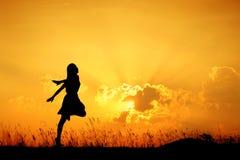 愉快的妇女跳跃和日落剪影 免版税库存照片
