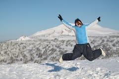 愉快的妇女跳跃在冬天山的,活跃女性享用的自然, 图库摄影
