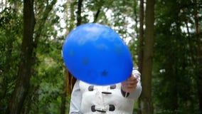 愉快的妇女身分和使用与在木头的一个蓝色气球在slo mo 影视素材