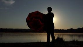 愉快的妇女转动她的棕色伞在日落在slo mo 影视素材
