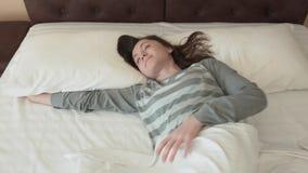 年轻愉快的妇女醒,拉扯自己并且下床 美丽的女孩从与微笑的床起来在她的面孔 股票录像