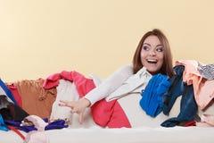 愉快的妇女采摘在杂乱屋子里穿衣  图库摄影