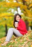 愉快的妇女饮用的咖啡在室外秋天的森林里 免版税图库摄影