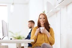 愉快的妇女饮用的咖啡或茶在办公室 免版税库存图片