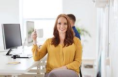 愉快的妇女饮用的咖啡或茶在办公室 库存图片