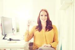 愉快的妇女饮用的咖啡或茶在办公室 免版税库存照片