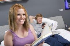 愉快的妇女读书小说在卧室 免版税库存照片