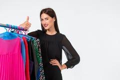 愉快的妇女购物和在白色背景隔绝的选择衣裳 免版税库存照片