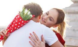 愉快的妇女从男朋友得到花束花 免版税库存照片