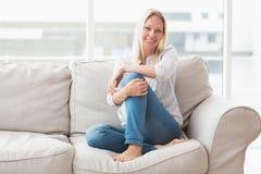 愉快的妇女画象坐沙发 免版税图库摄影