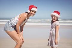愉快的妇女画象有戴圣诞老人帽子的女儿的在海滩 免版税库存图片