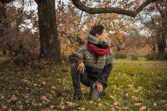 愉快的妇女画象获得与叶子的乐趣在秋天 图库摄影