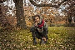 愉快的妇女画象获得与叶子的乐趣在秋天 库存照片
